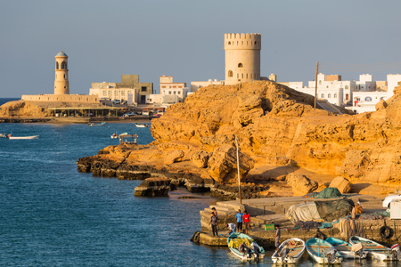 SUR, OMAN - NOVEMBER 25, 2017: View of the Al Ayjah town, watchtower and lighthouse in the bay of Sur, Oman. In the foreground, fishermen working at the port. Editorial