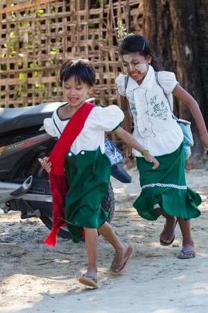 NGAPALI BEACH, MYANMAR - December 3, 2014: two little girls go to school school in the fishing village Jade Taw, south of hotels in Ngapali beach.