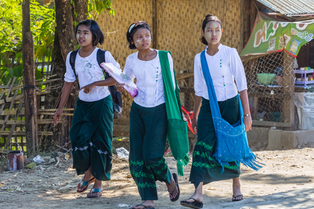 NGAPALI BEACH, MYANMAR - December 3, 2014: Three little girls go to school school in the fishing village Jade Taw, south of hotels in Ngapali beach.