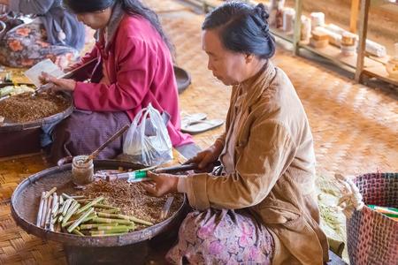 INLE LAKE, MYANMAR - DECEMBER 01, 2014: Women rolling traditional cheroot cigars in a craft workshop at Nam Pam village, on Inle Lake, Myanmar