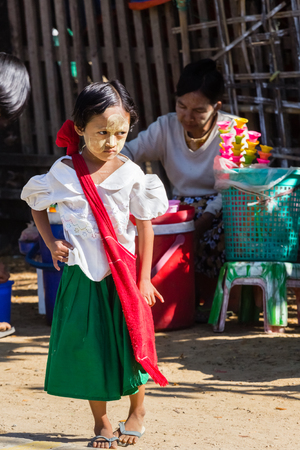 NGAPALI BEACH, MYANMAR - December 3, 2014: an unidentified child goes to elementary school in the fishing village Jade Taw, south of hotels in Ngapali beach.