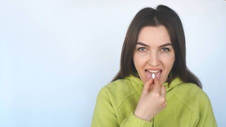 Young woman taking a tablet. Hand with a pill and the mouth. Food Supplements, health care concept.