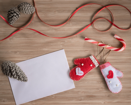 White and red wooly mittens on wooden background, Christmas concepts Banco de Imagens