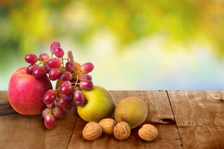 Autumn harvested fruits on the wooden table background. Apple, pears, kiwifruit, grapes, walnuts.