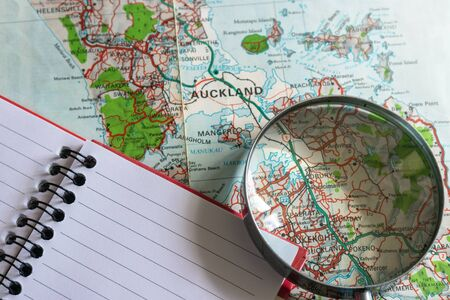 Magnifying glass and notepad over an old map of New Zealand