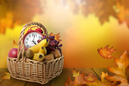 Fruit basket with alarm clock, autumn leaves background, daylight saving time concept