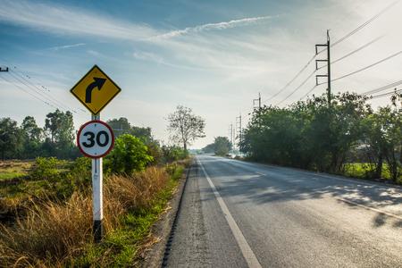 Signo de flecha negra en tablero amarillo al lado de la calle con árboles y cielo azul, nubes.