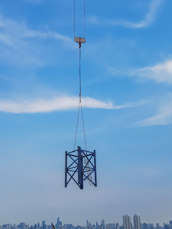 Mast crane was raised in the air at the top of the tower white blue sky background. Stock Photo