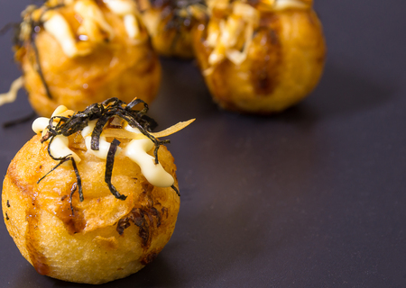 sprinkled: Takoyaki, Japanese food is popular with both Japanese and Thais. It is a mixture of crushed flour. Squid stuffed in the middle or crab stuffed with mayonnaise and seaweed sprinkled on top. Stock Photo