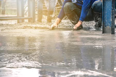 Hombre sentado y usando una espátula de madera para cemento después de verter concreto premezclado sobre refuerzo de acero para hacer la carretera mezclando móvil la hormigonera. Foto de archivo