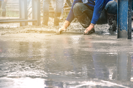 Mann sitzt und benutzt einen Holzspatel für Zement, nachdem er Transportbeton auf Stahlbewehrung gegossen hat, um die Straße durch Mischen des Betonmischers mobil zu machen. Standard-Bild