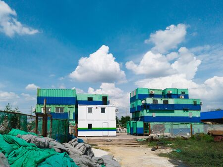 Office containers  are arranged stacked in storage before using with beautiful cloud and blue sky.