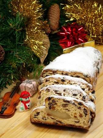 Slices of stollen on a wooden board with Christmas themed decorations photo