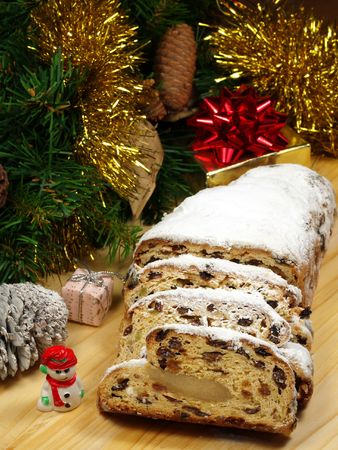 themed: Slices of stollen on a wooden board with Christmas themed decorations