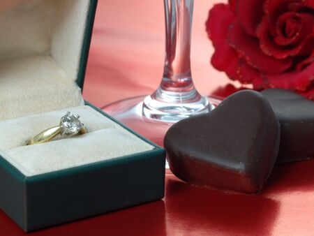 Chocolate hearts with champagne glass and engagement ring on reflective red background photo