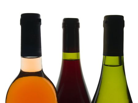 bacchus: Backlit shot of red, rose and white wine bottles Stock Photo