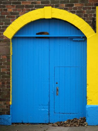 Blue door with yellow arched frame in red brick wall       photo