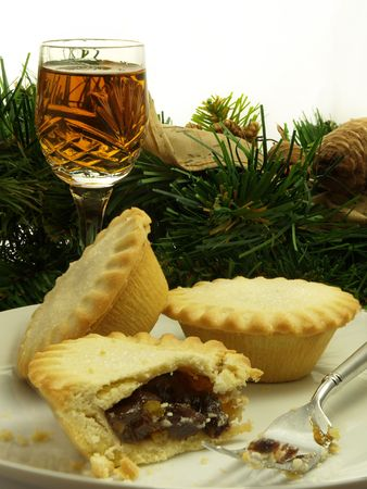 tipple: Plate of mince tarts with a glass of sherry and traditional Christmas decor in background Stock Photo