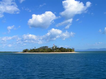 ble: Coral island in a ble sea whith blue sky and white couds behind
