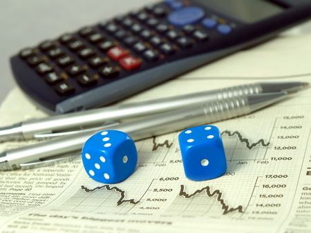 Calculator pens dice and financial pages of a newspaper. Stock Photo - 2656114