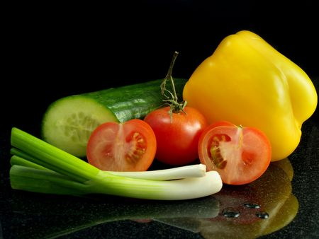 Half cucumber, yellow bell pepper, spring onions and two tomatoes on granite work surface, with reflection and black background