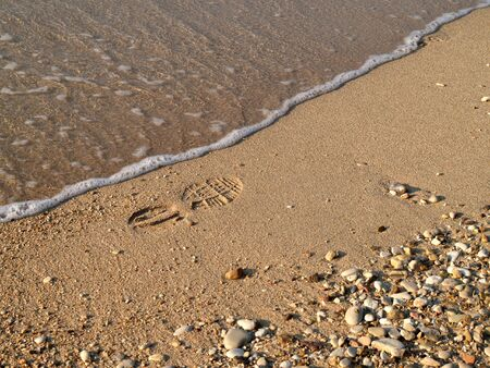 shoeprint: Shoe-print in wet sand with wave Stock Photo