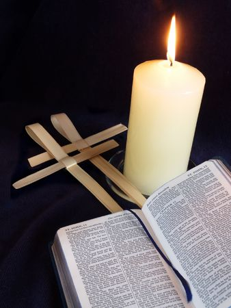 Lit candle with bible open at Palm Sunday story, and palm crosses Stock Photo