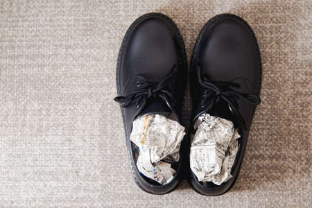 Stuff the shoes with newspaper and dry them. Wet, damp shoes.