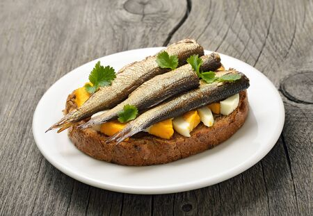 sprats: Sandwich with sprats and egg on wooden table, close up