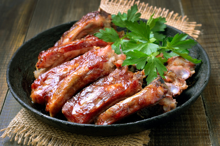Roasted pork ribs in frying pan, close up Stock Photo