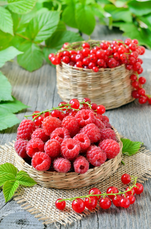 red currant: Raspberries in wicker basket and red currant on wooden table Stock Photo