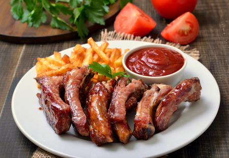 close up view: Barbecue pork ribs and vegetables on white plate, close up view