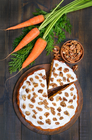 walnut cake: Carrot cake and fresh carrot on wooden table, top view