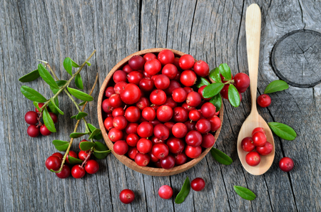 Red lingonberry in wooden bowl on rustic surface, top view