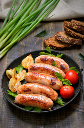 Barbecue sausages in frying pan on wooden table, top view