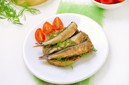 sardine can: Appetizing sandwiches with sprats  on white plate