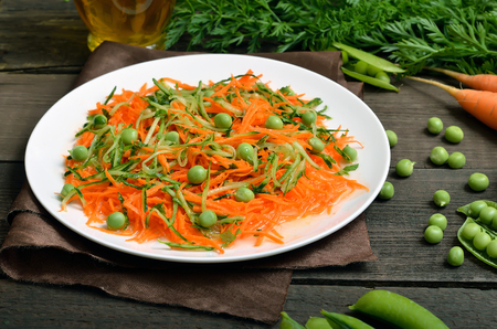 Vegetarian food. Vegetable salad with carrot, cucumber and green peas on white plate Stock Photo