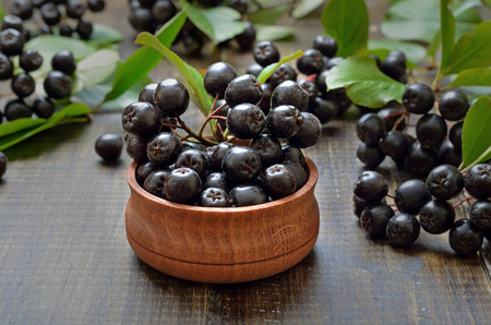 Black chokeberry in wooden bowl, close up