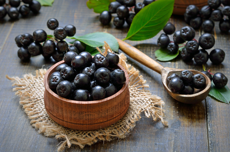 Black chokeberry (Aronia melanocarpa) in wooden bowl, fresh black chokeberry  in wooden spoon Stock Photo