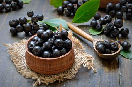 Czarne aronii (aronii melanocarpa) w drewniane miski, świeże czarne aronii w drewnianą łyżką Zdjęcie Seryjne