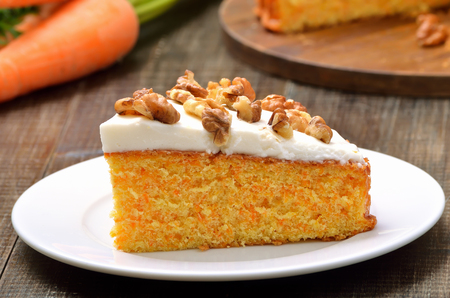 Piece of carrot cake with icing decorated walnut on white plate, close up