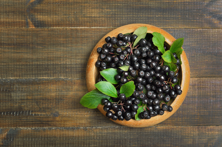 Fresh black chokeberry on wooden table, top view
