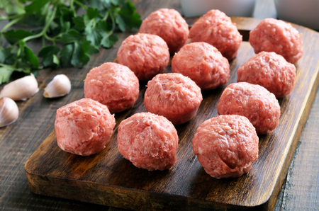 Raw meatballs on a cutting board, close up