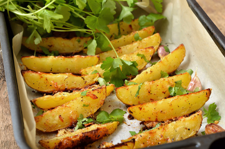 Baked potato wedges with spices and herbs, close up Reklamní fotografie