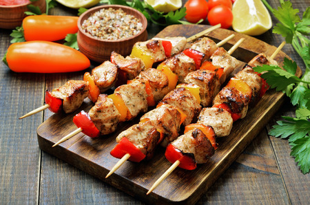 Fried chicken kebabs on a cutting board and fresh vegetables on wooden table Banque d'images