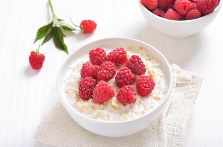 Tasty oatmeal porridge with raspberries, close up view