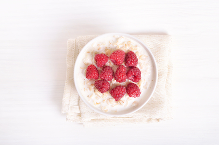 Tasty porridge with raspberries on white background, top view Stock Photo