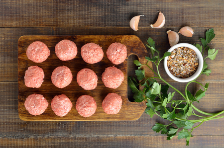 Raw meatballs on the cutting board on wooden surface, top view