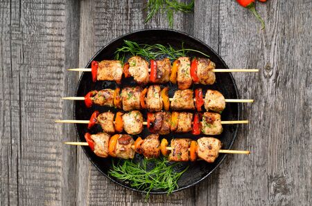 Grilled chicken kebabs with vegetables on wooden table, top view