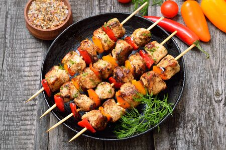 Chicken kebab with bell pepper in frying pan, close up